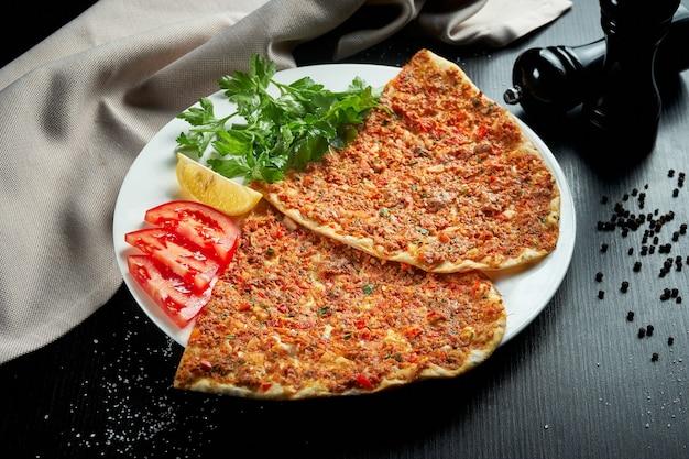Lahmacun ist ein beliebtes türkisches gericht. dünne knusprige tortilla mit gehacktem lammfleisch, tomaten und paprika auf schwarzem tisch