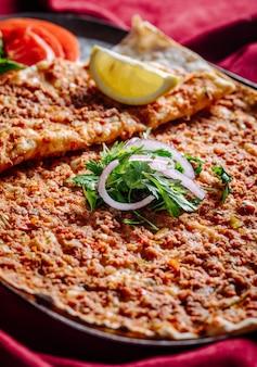 Lahmacun mit fleischfüllung, serviert mit gehackter zwiebel, petersilie, tomate und zitrone.