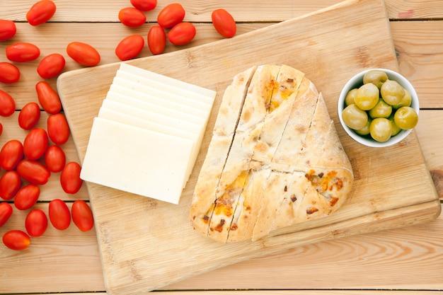 Laib bio-brot auf holzhintergrund mit käse, oliven und tomaten. frisches vollkornbrot. natürliches lebensmittelkonzept.
