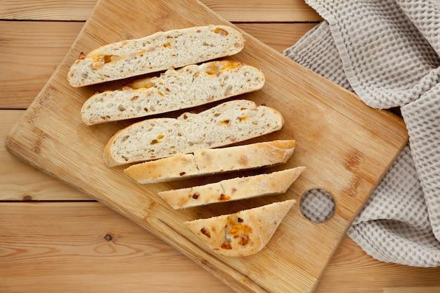 Laib bio-brot auf holzuntergrund mit käse und schinken. frisches vollkornbrot. natürliches lebensmittelkonzept.