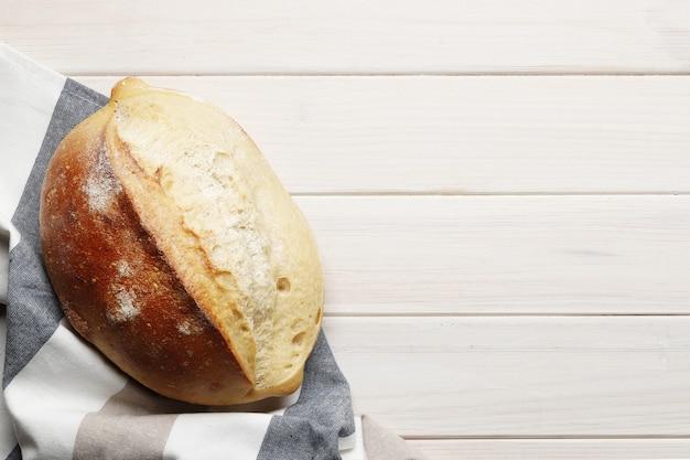 Laib hausgemachtes brot mit küchenzubehör und backzutaten auf einem holztisch mit platz für text. frische bäckerei.