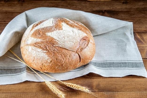 Laib integralen brotes auf der küchenserviette und auf dem holztisch. gesundes getreidebrot.