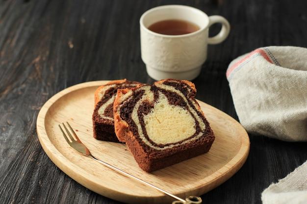 Laib marmorkuchenscheibe auf schwarzem holzuntergrund, serviert mit tee