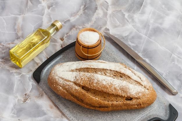 Laib roggenbrot auf einem schneidebrett, eine flasche sonnenblumenöl, ein messer und ein hölzerner salzkeller auf dem küchentisch. ansicht von oben.