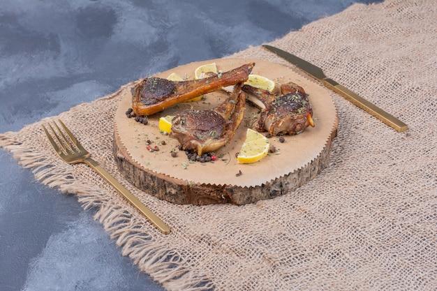 Lammfleisch auf holzbrett mit zitronenscheiben und besteck auf tischdecke.