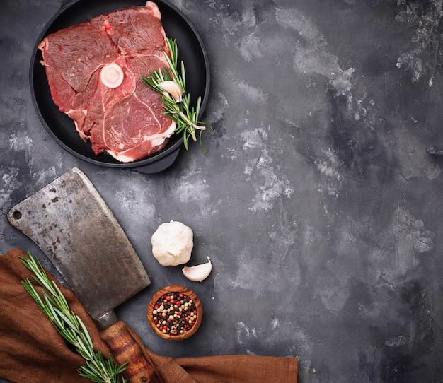Lammfleisch mit rosmarin, gewürzen und hackmesser.