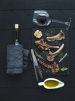 Lammkarree mit knoblauch, rosmarin, gewürzen auf schiefertablett, weinglas, öl in einer untertasse und flasche über schwarzer holzoberfläche