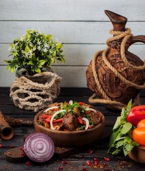 Lammkebabsalat gemischt mit tomaten, zwiebelscheiben und frischen kräutern
