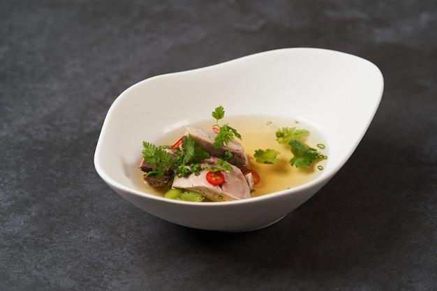 Lammsuppe mit chili-pfeffer, tomaten, petersilie und bohnen in einer weißen schüssel