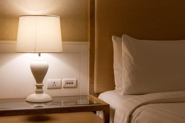 Lampe auf einem nachttisch neben dem klassischen bett.