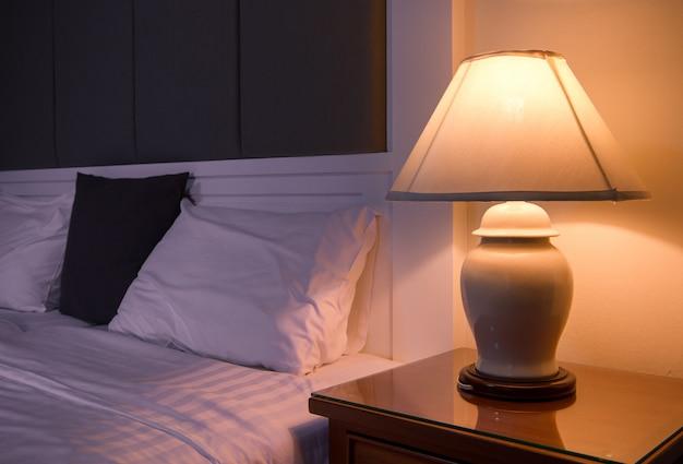 Lampe auf einem nachttisch neben einem klassischen bett.