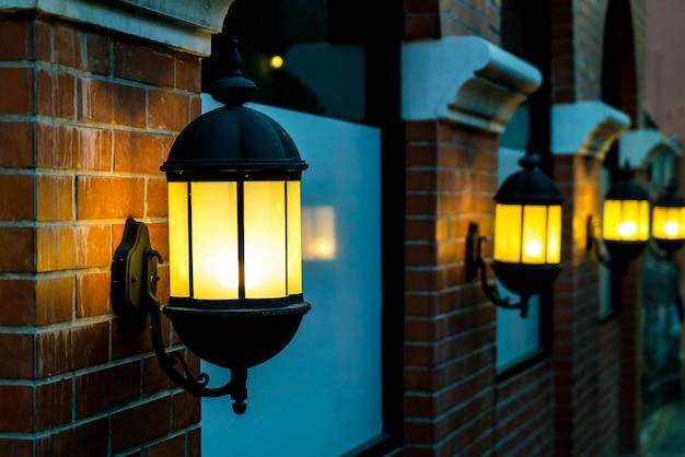 Lampe gegen eine rote mauer in der nacht.