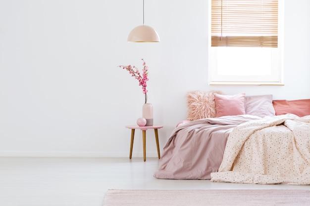 Lampe über dem tisch mit blumen in rosafarbenem pastellschlafzimmer mit fenster über dem bett. echtes foto mit platz für deinen sessel
