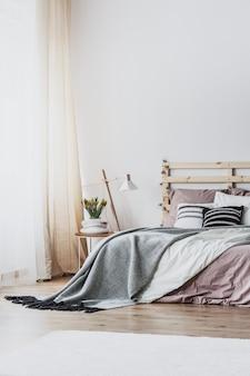 Lampe und pflanze auf dem tisch neben dem holzbett mit grauen und rosafarbenen blättern im schlafzimmerinnenraum. echtes foto