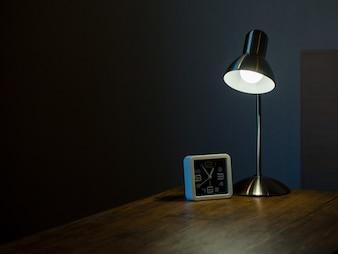 Lampe und Uhr in der Dunkelkammer mit Licht- und Schattenkonzept