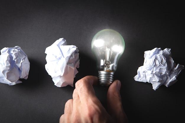 Lampe und zerknitterte papiere auf dem tisch. konzeptidee