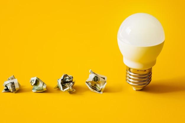 Lampe und zerknittertes geld auf gelb.