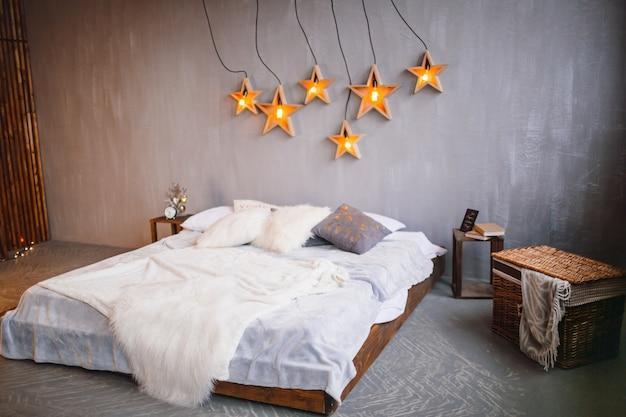 Lampen in form von sternen hängen über einem großen bett