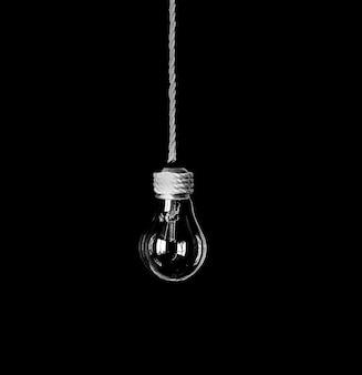 Lampenbirne, die am seil hängt, isoliert auf schwarzem hintergrund. neues ideenkonzept.
