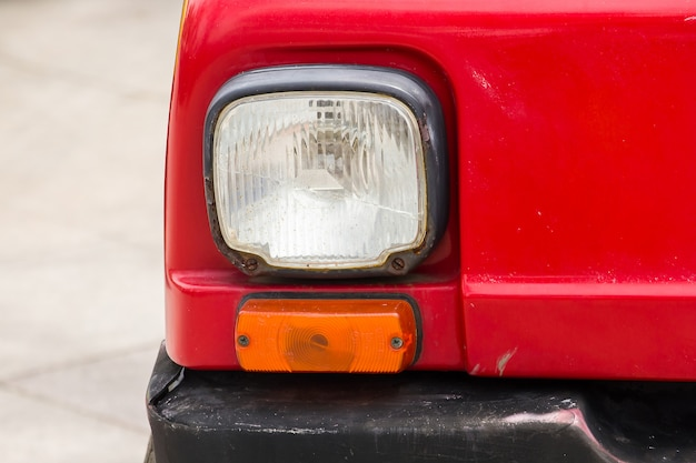 Lampenteile vor dem roten oldtimer