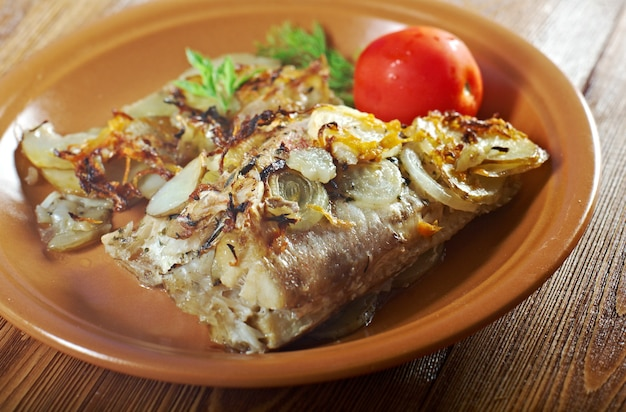 Land im bauernstil. gebackener barsch mit kartoffeln und zwiebeln gebacken