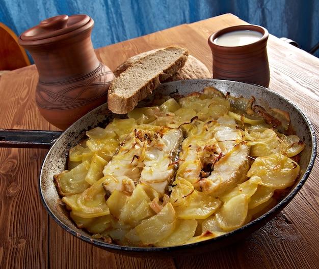 Land-kabeljau nach bauernart mit kartoffeln und zwiebeln gebacken