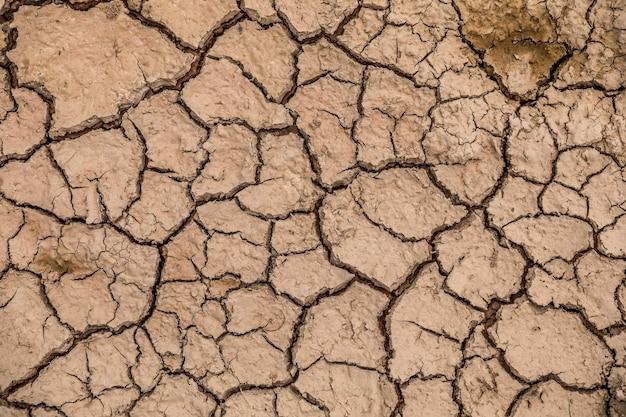 Land mit trockenem und rissigem boden. hintergrund der globalen erwärmung