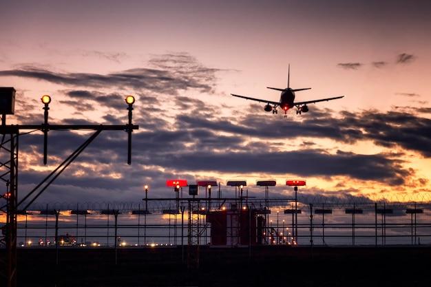 Landeflugzeug und wünschelruten-vogelschrecken am flughafen gegen schönen rosa sonnenuntergang.