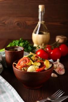 Landeintopfgericht mit fleisch, kartoffel, tomatenzwiebel und käse in der lehmschüssel auf rustikaler tabelle diente für abendessen
