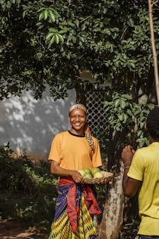 Landfrau, die frische früchte hält