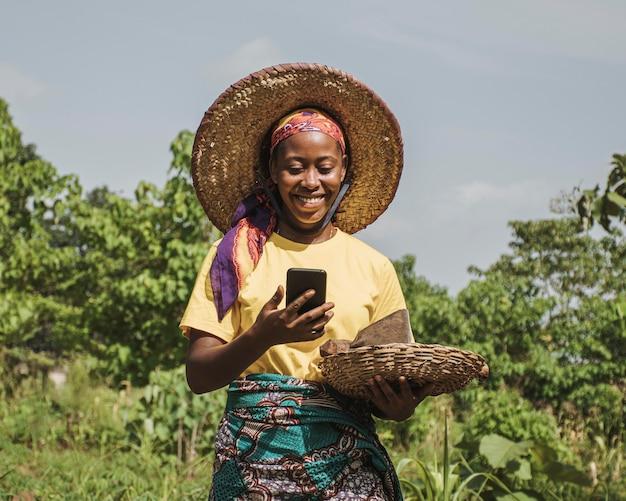 Landfrau, die ihr telefon überprüft