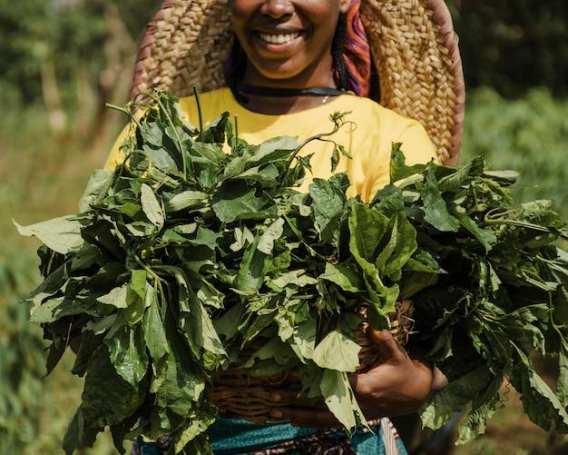 Landfrau, die pflanzenblätter hält