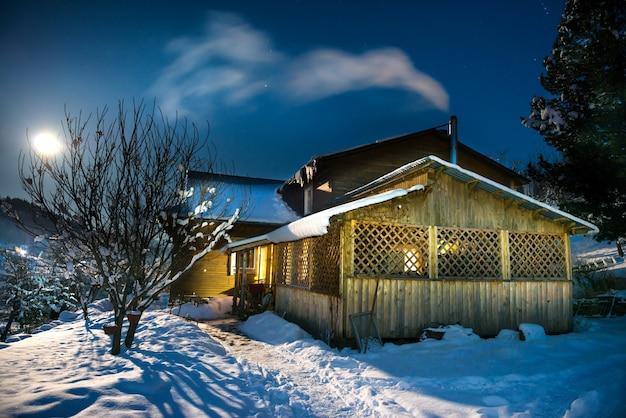 Landhaus aus holz im schnee in der winternacht unter blauem dunklem himmel mit sternen und mond