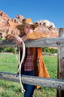 Landhausstil-modeporträt einer schönen langhaarigen blonden jungen frau, die einen cowboyhut trägt