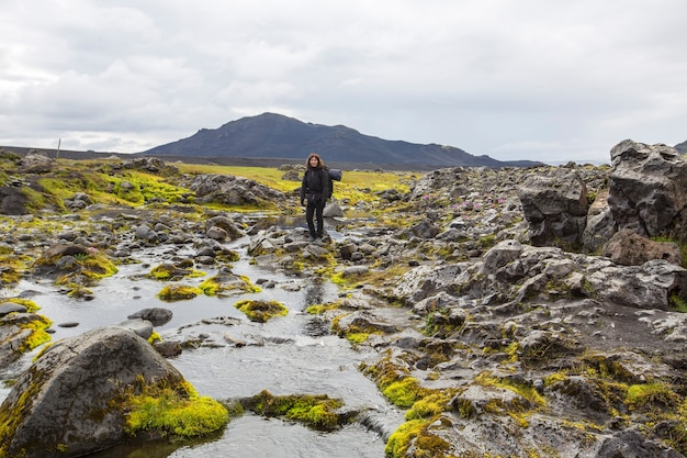 Landmannalaugar, island »; august 2017: eine junge frau überquert einen fluss im landmannalaugar-trekking