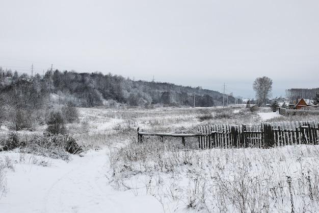 Landschaft am bewölkten wintertag von schneebedeckten feldern und wäldern
