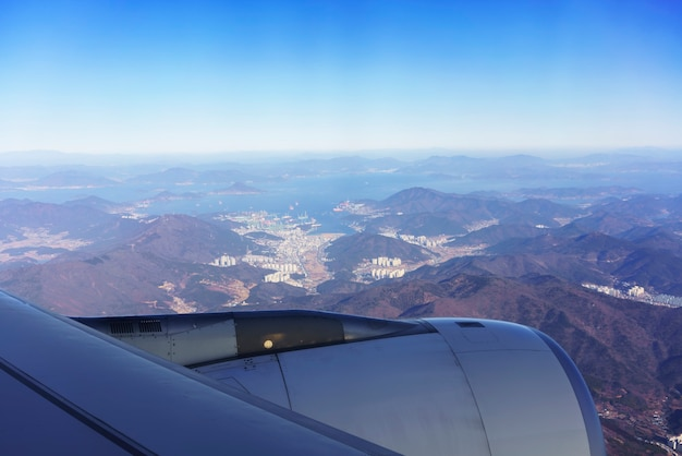 Landschaft aus dem flugzeugfenster mit blick auf den blauen himmel, die südkoreanische halbinsel, die angrenzenden inseln und die metropole busan am morgen, südkorea