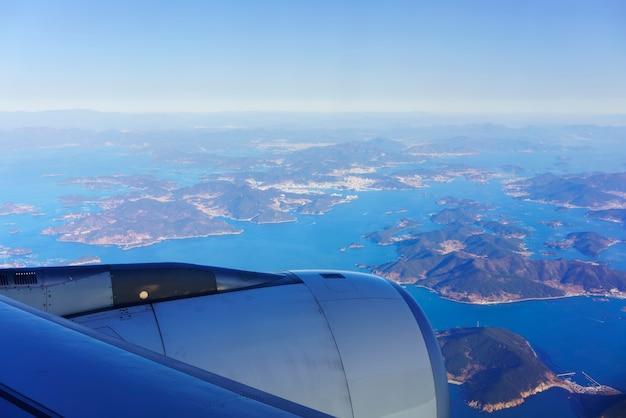 Landschaft aus dem flugzeugfenster mit blick auf den blauen himmel und die südkoreanische halbinsel und ihre angrenzenden inseln am morgen