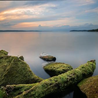 Landschaft bei sonnenuntergang mit strukturiertem vordergrund und langzeitbelichtung