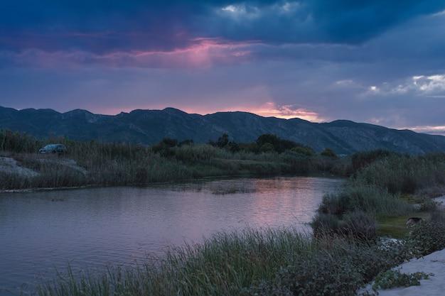 Landschaft bergstrand entlang des flusses bei sonnenuntergang mit lila himmel n xeraco, valencia