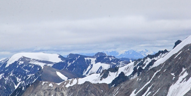 Landschaft der berge bedeckt im schnee unter einem bewölkten himmel während des tages