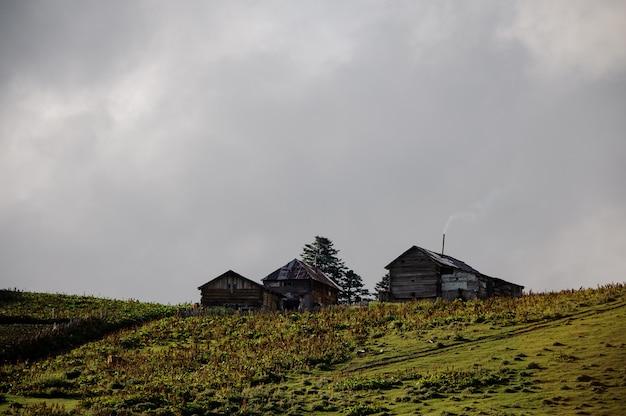Landschaft der drei holzhäuser auf dem hügel