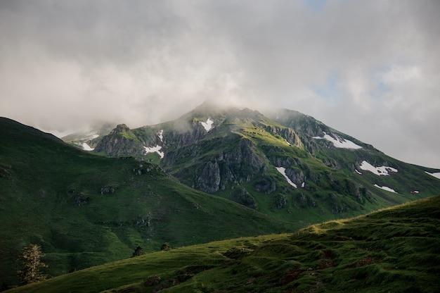 Landschaft der felsigen berge unter dem weißen nebel bedeckt mit gras mit den schneeresten
