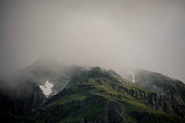 Landschaft der grünen berge bedeckt mit weißem nebel