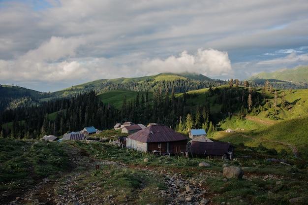 Landschaft der holzhäuser, die auf dem hügel auf dem backgound des klaren himmels und der grünen berge stehen