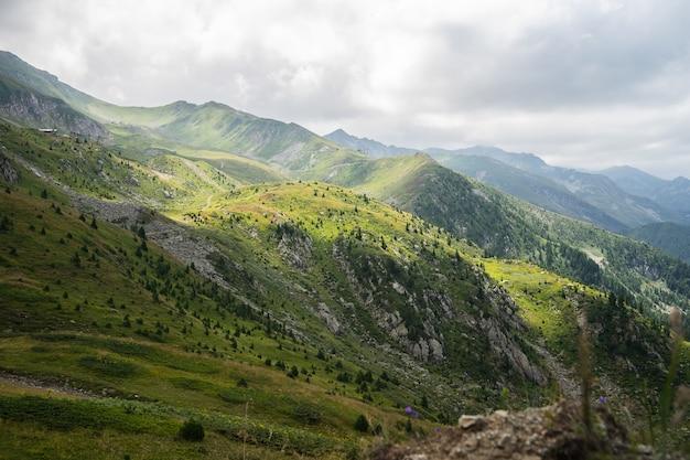 Landschaft der hügel bedeckt im grün mit felsigen bergen unter einem bewölkten himmel auf dem hintergrund