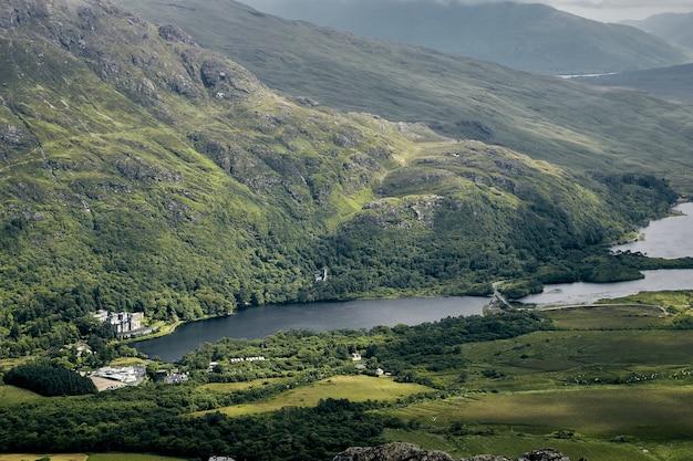Landschaft der hügel, die im grün unter einem bewölkten himmel im connemara-nationalpark, irland bedeckt werden