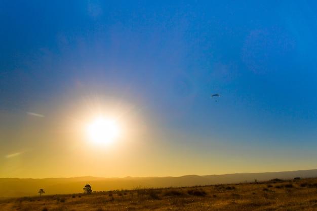 Landschaft der sonnenfinsternis in den bergen und gleitschirmfliegen im himmel