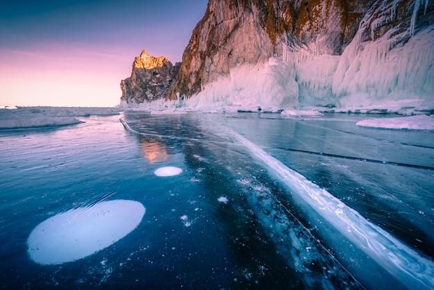 Landschaft des berges bei sonnenuntergang mit natürlichem brechendem eis in gefrorenem wasser am baikalsee, sibirien, russland.