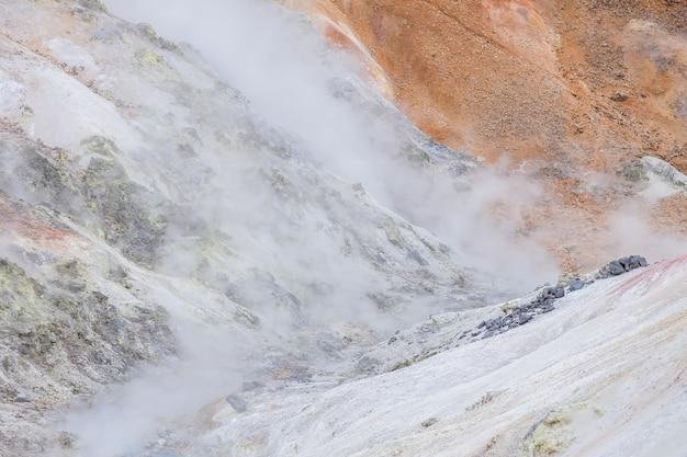 Landschaft des berges im bereich der heißen quelle mit kleinem heißem strom mit etwas dampf